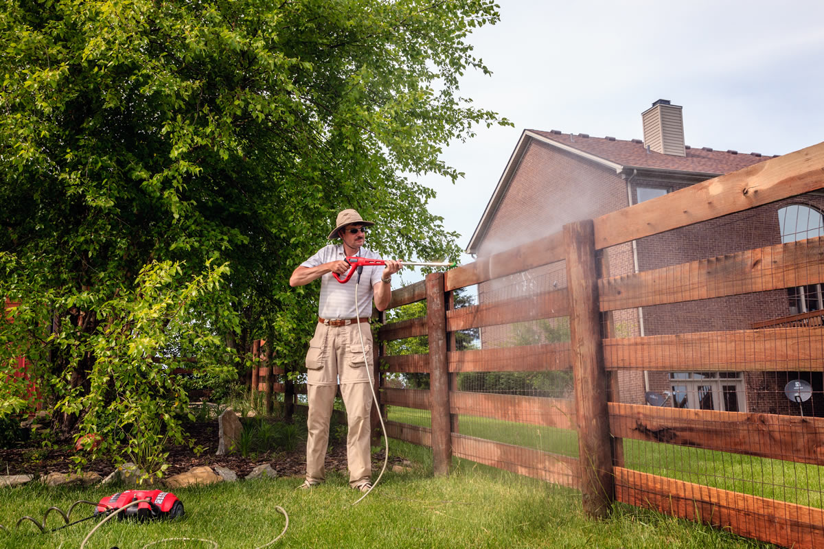 Picture of a guy power washing his fence.  Prevention.